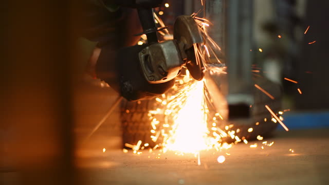 industry worker grinding metal with angle grinder - rettificatrice video stock e b–roll