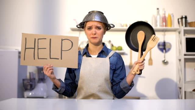 vídeos y material grabado en eventos de stock de ama de casa inexperta pidiendo ayuda en la cocina, el uso de la olla en la cabeza, broma - receta instrucciones