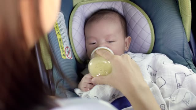 Infant baby boy buckled into his car seat and drinking milk