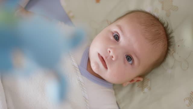 vídeos de stock, filmes e b-roll de bebê de observação menino infantil móvel enquanto estava deitado na cama - mobile