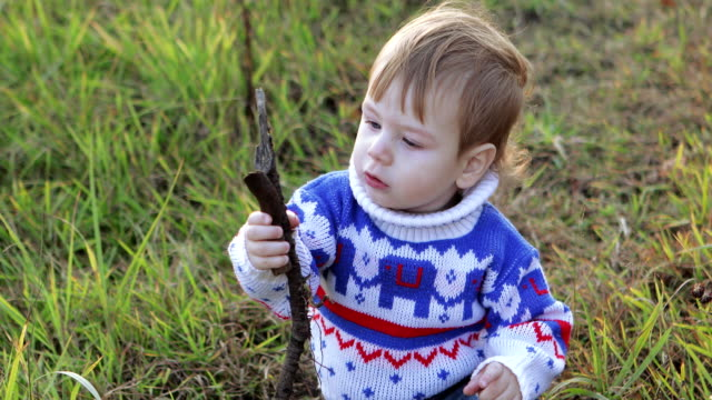 Infant boy playing a stick video
