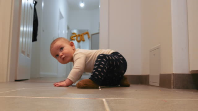 Infant Crawling on Tiled Floor Infant crawling on tiled floor at home. Full length. tile stock videos & royalty-free footage