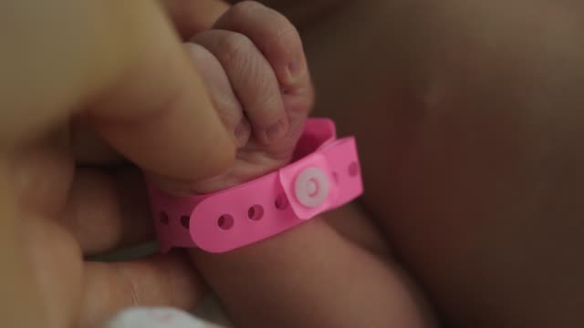 infant newborn hand arm wrist pink girl band hospital  identification wristband