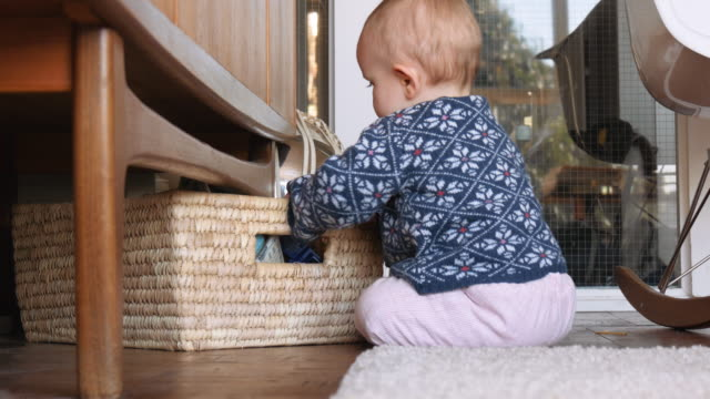 Infant Playing with Basket Under Living Room Cupboard