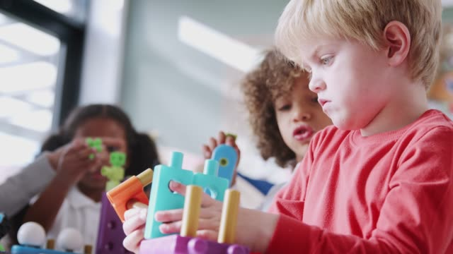 Infant school boy using educational construction toys with his classmates, low angle, close up Infant school boy using educational construction toys with his classmates, low angle, close up playroom stock videos & royalty-free footage