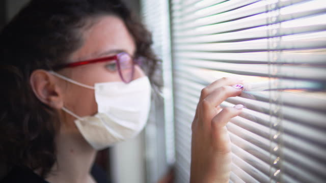 Infected corona virus covid-19 woman isolated in hospital room look over window blinds wearing protective mask
