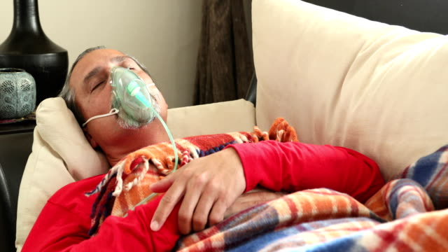 vídeos de stock e filmes b-roll de infected sick man is breathing through a nebulizer mask - covid hospital bed respirator