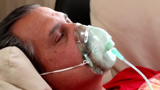 stockvideo's en b-roll-footage met geïnfecteerde zieke man ademt door middel van een vernevelaar masker - ventilator bed