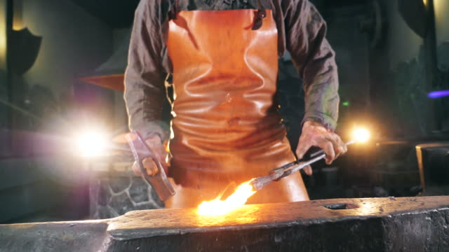 Inflamed metal is getting hammered by the blacksmith. Slow motion. video