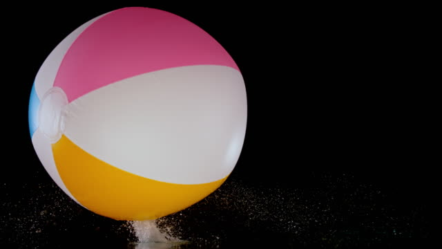 SLO MO LD Inflatable beach ball bouncing on black surface