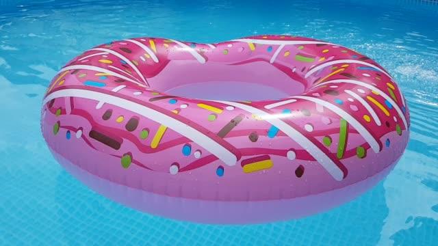 uppblåsbar ring, rosa munk snurrar i poolen. uppblåsbar badcirkel - inflatable ring bildbanksvideor och videomaterial från bakom kulisserna