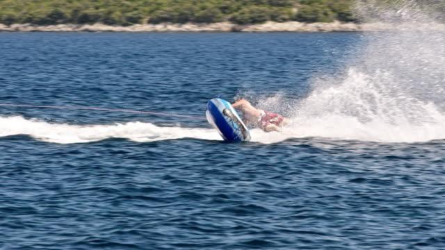 slo mo inflatable tube ride at the seaside in sunshine - rimorchiatore video stock e b–roll