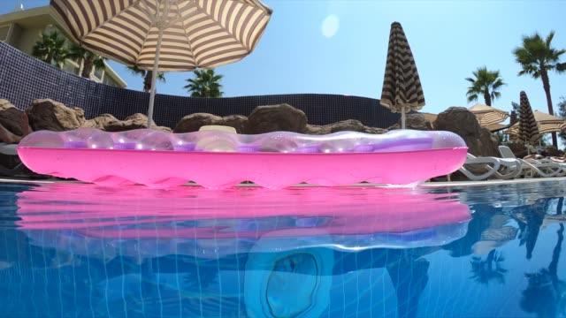 vídeos de stock, filmes e b-roll de os colchões de água infláveis flutuam na água - inflável