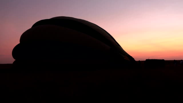 CLOSE UP: Inflating big safari balloon on open field in early morning at dawn video