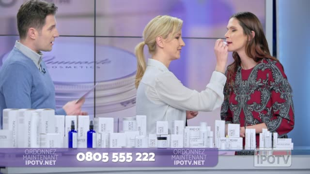 Infomercial montage in French: Woman placing some lip salve of the cosmetic line she is presenting on the female model's lips while talking to the male host of the infomercial show