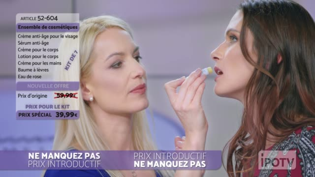 Infomercial montage in French: Woman presenting a lip salve from the cosmetic line on an infomercial show putting some on the female model's lips while talking to the female host