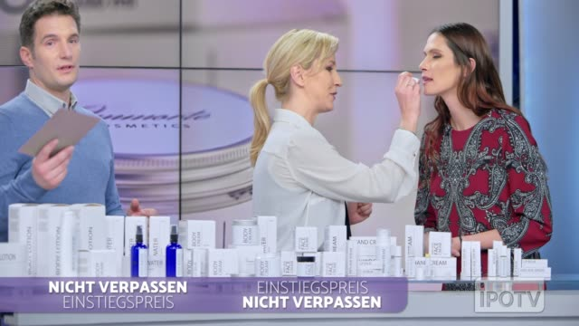 Infomercial montage in German: Woman placing some lip salve of the cosmetic line she is presenting on the female model's lips while talking to the male host of the infomercial show