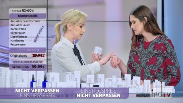 infomercial montage in deutscher sprache: frau präsentiert eine kosmetiklinie auf einer infomercial show, die etwas sahne auf dem weiblichen modell reibt, während sie mit dem männlichen wirt spricht und das produkt erklärt - montage filmtechnik stock-videos und b-roll-filmmaterial