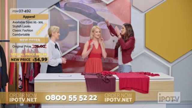 uk infomercial montage: stylist in einer tv-show, die über das kleid spricht, das das model trägt, und eine halskette um ihren hals legen, während sie mit der weiblichen gastgeberin spricht - kurzwaren stock-videos und b-roll-filmmaterial