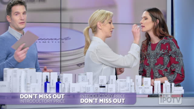 UK infomercial montage: Woman placing some lip salve of the cosmetic line she is presenting on the female model's lips while talking to the male host of the infomercial show