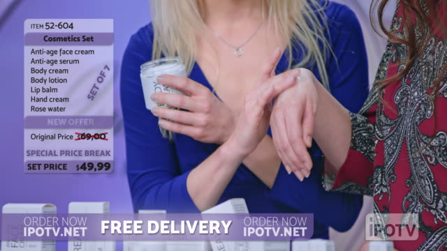 US infomercial montage: Woman presenting a cosmetic line on an infomercial show rubbing cream onto the hand of a female model while talking to the female host