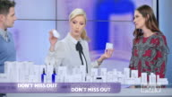 istock US infomercial montage: Woman presenting a cosmetic line on an infomercial show rubbing some cream on the female model while talking to the male host and explaining the product 1272418270