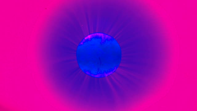 Infrared pill dissolving in water looking like star igniting and sending flares of energy heating in space abstract background video