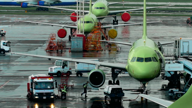 infrastruktur international airport entfernt. flugzeuge auf der website, die mitarbeiter die erforderlichen wartungsarbeiten geschlossen. - asphalt stock-videos und b-roll-filmmaterial