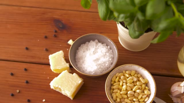 ingredients for basil pesto sauce on wooden table food and culinary concept - parmesan cheese, pine nuts, sea salt and garlic for basil pesto sauce making on wooden table pine nut stock videos & royalty-free footage