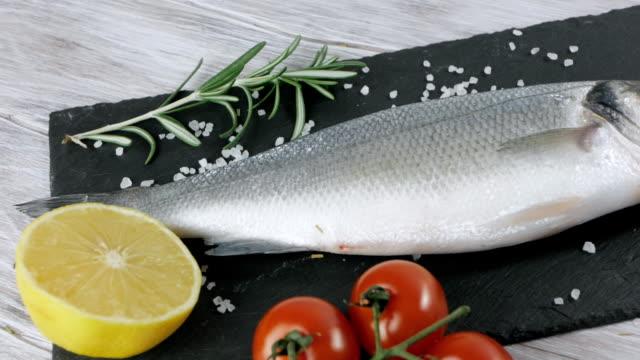 ingredients for cooking fish. fresh sea bass, lemon, cherry tomato, rosemary - mar mediterraneo video stock e b–roll
