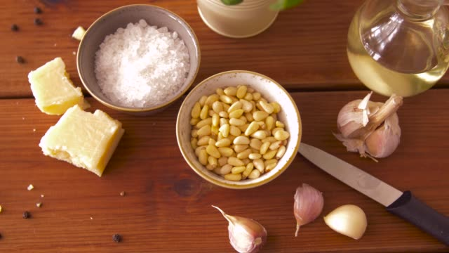 ingredients for pesto sauce on wooden table food and culinary concept - parmesan cheese, pine nuts, sea salt, garlic and olive oil for pesto sauce making on wooden table pine nut stock videos & royalty-free footage