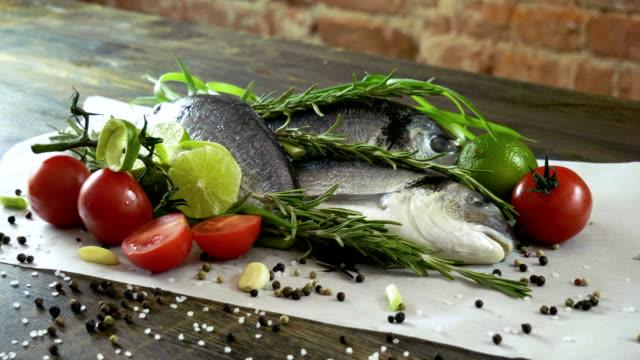 ingredients for preparation fish. fresh sea bass, green onions, lime, garlic cloves, salt, black pepper, rosemary. 4k - морской окунь стоковые видео и кадры b-roll