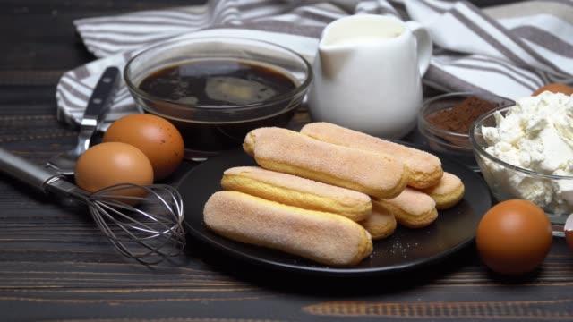 ingredienti per la tradizionale torta al tiramisù su sfondo legno - theobroma video stock e b–roll