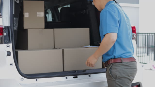 In-Home Delivery concept. Delivery Man loading his shipping van with  parcel post in cardboard boxes and checking stock of parcel post before delively to costomer In-Home Delivery concept. Delivery Man loading his shipping van with  parcel post in cardboard boxes and checking stock of parcel post before delively to costomer post office stock videos & royalty-free footage