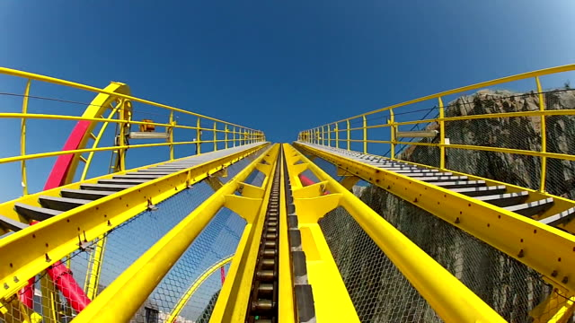 initial peak on a yellow roller coaster - luna park video stock e b–roll