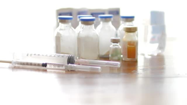 enjeksiyon aşı şişeleri tıbbi şırınga yakın çekim beyaz arka plan ve ahşap masa - doping stok videoları ve detay görüntü çekimi