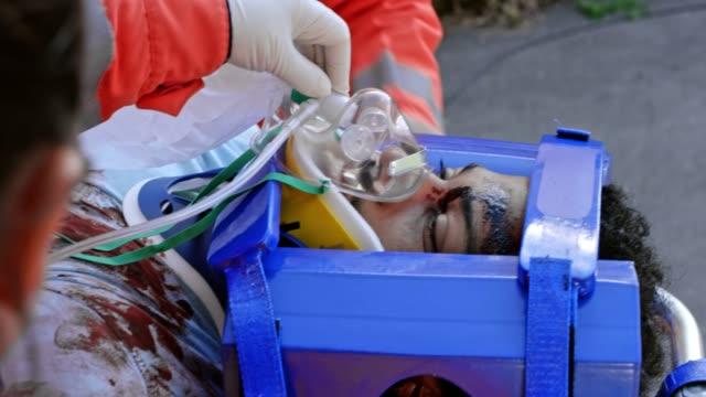 verletzten afrikanisch-amerikanischer mann gegeben sauerstoffmaske während geladen in den krankenwagen durch die sanitäter-team - sauerstoff stock-videos und b-roll-filmmaterial