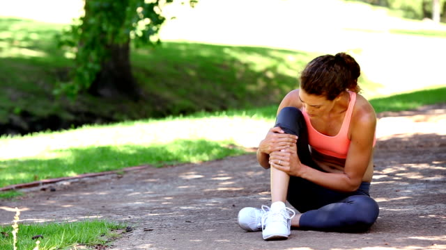 Injured fit woman touching her ankle in the park Injured fit woman touching her ankle in the park on a sunny day ankle stock videos & royalty-free footage
