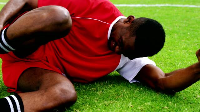 Injured football player lying on grass Injured football player lying on grass in the field physical injury stock videos & royalty-free footage