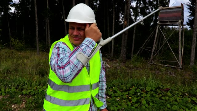 Injured forest worker in windy day with crutches at the forest Injured forest worker in windy day with crutches at the forest crutch stock videos & royalty-free footage