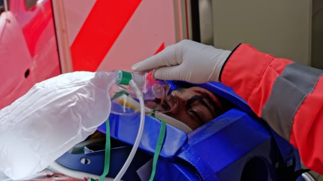 injured man being loaded into the ambulance with the doctor by his side preparing him for transport - paramedic stock videos & royalty-free footage