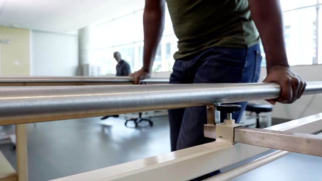 Injured military veteran uses parallel bars for assistance in walking in rehabilitation center Unrecognizable injured male soldier uses parallel bars in a rehab center to help him walk during his recovery. veteran stock videos & royalty-free footage