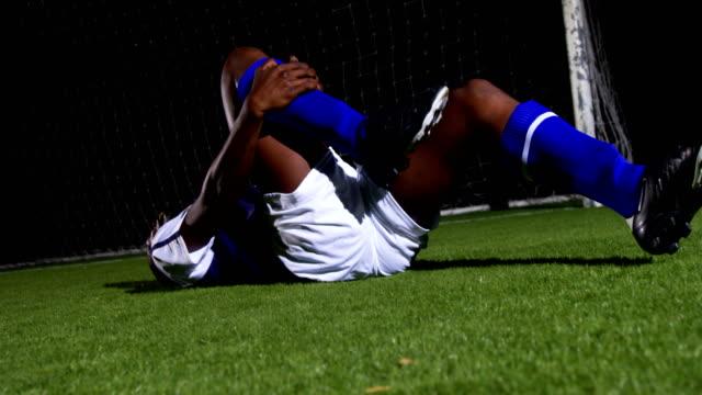 stockvideo's en b-roll-footage met gewonde voetballer liggend 4k - samen sporten