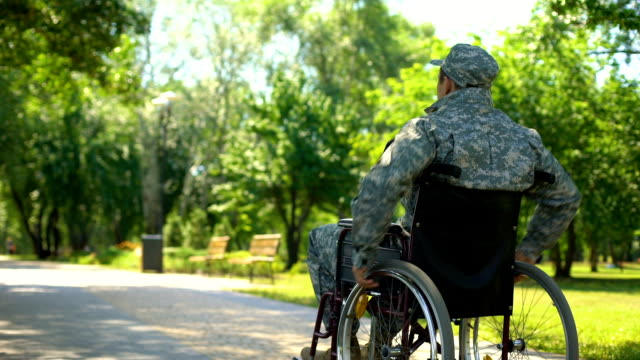 injured soldier in wheelchair moving in park, social military support, pension - military lifestyle stock videos & royalty-free footage