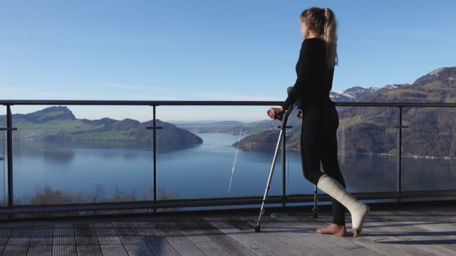 Injured woman uses crutches to walk across balcony, view over lake Recovering from ankle injury at home crutch stock videos & royalty-free footage