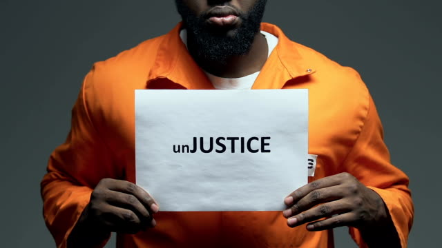 Injustice word on cardboard in hands of African-American prisoner, disorder Injustice word on cardboard in hands of African-American prisoner, disorder civil rights stock videos & royalty-free footage
