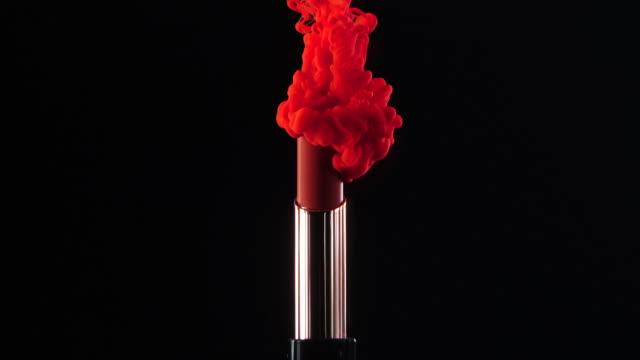 stockvideo's en b-roll-footage met inkt daling vallen naar lippenstift met zwarte achtergrond in slow motion - make up
