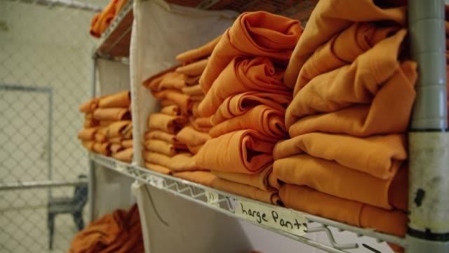 inmate uniforms sit on a shelf - prigione video stock e b–roll