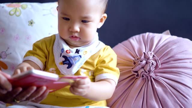 innocence little boy playing smartphone - solo neonati maschi video stock e b–roll
