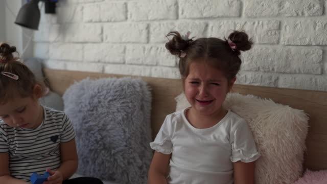 きょうだいと遊びながら家で泣いている無邪気な子供 - 兄弟姉妹点の映像素材/bロール